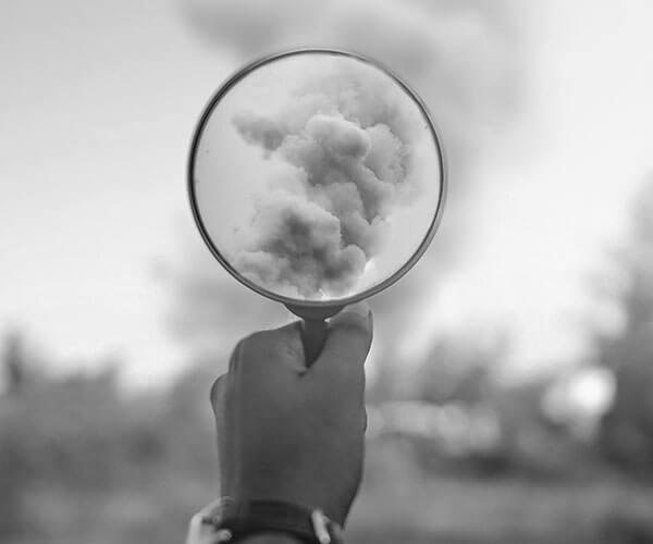 picture of a hand holding a magnified glass viewing a cloud formation